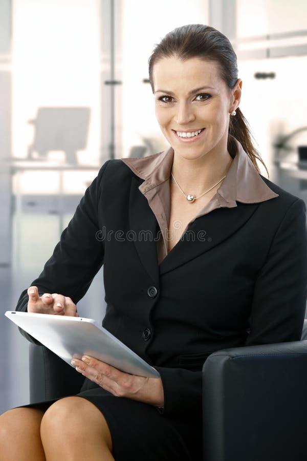Μέσος-ενήλικη επιχειρηματίας που εργάζεται με την ταμπλέτα στοκ εικόνα