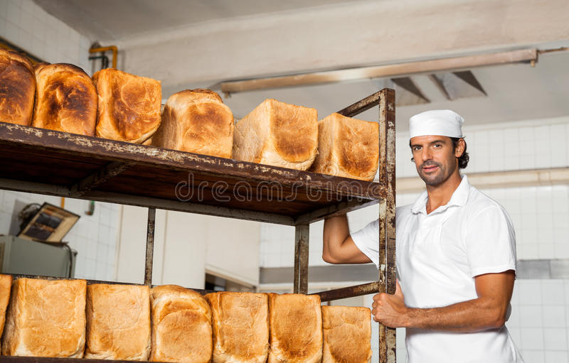 Μέσος ενήλικος αρσενικός Baker που υπερασπίζεται το ράφι ψωμιού στοκ φωτογραφίες με δικαίωμα ελεύθερης χρήσης