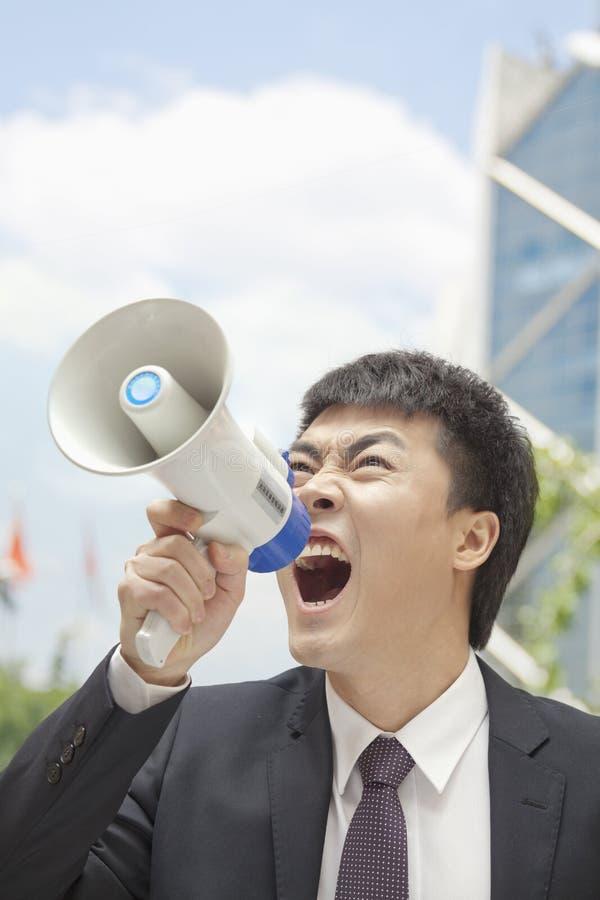 Μέσος ενήλικος επιχειρηματίας που φωνάζει megaphone, υπαίθρια, Πεκίνο, Κίνα στοκ εικόνα