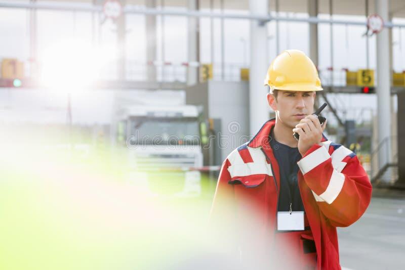 Μέσος ενήλικος εργαζόμενος που χρησιμοποιεί walkie-talkie στη ναυτιλία του ναυπηγείου στοκ φωτογραφία