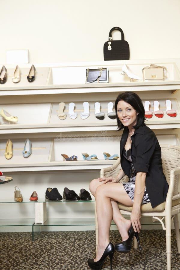Μέσος ενήλικος θηλυκός πελάτης που προσπαθεί στα τακούνια στο κατάστημα παπουτσιών στοκ φωτογραφία