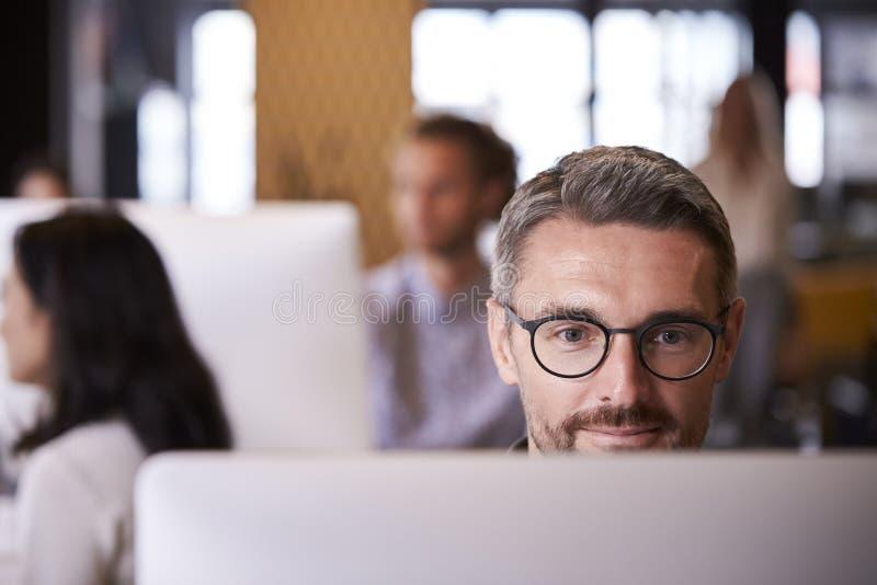 Μέσος ηλικίας άσπρος αρσενικός δημιουργικός χρησιμοποιώντας έναν υπολογιστή σε ένα πολυάσχολο γραφείο, εκλεκτική εστίαση, κλείνει στοκ φωτογραφία με δικαίωμα ελεύθερης χρήσης
