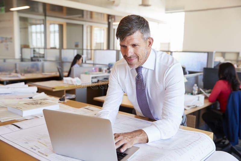 Μέσος ηλικίας αρσενικός αρχιτέκτονας που χρησιμοποιεί το lap-top στο ανοικτό γραφείο σχεδίων στοκ εικόνα με δικαίωμα ελεύθερης χρήσης