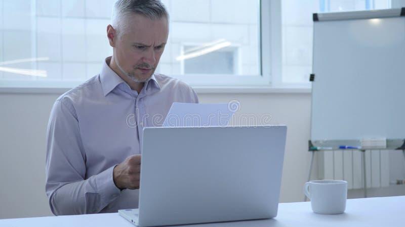 Μέσος ηλικίας επιχειρηματίας που εργάζεται στα έγγραφα, γραφική εργασία στοκ εικόνα με δικαίωμα ελεύθερης χρήσης