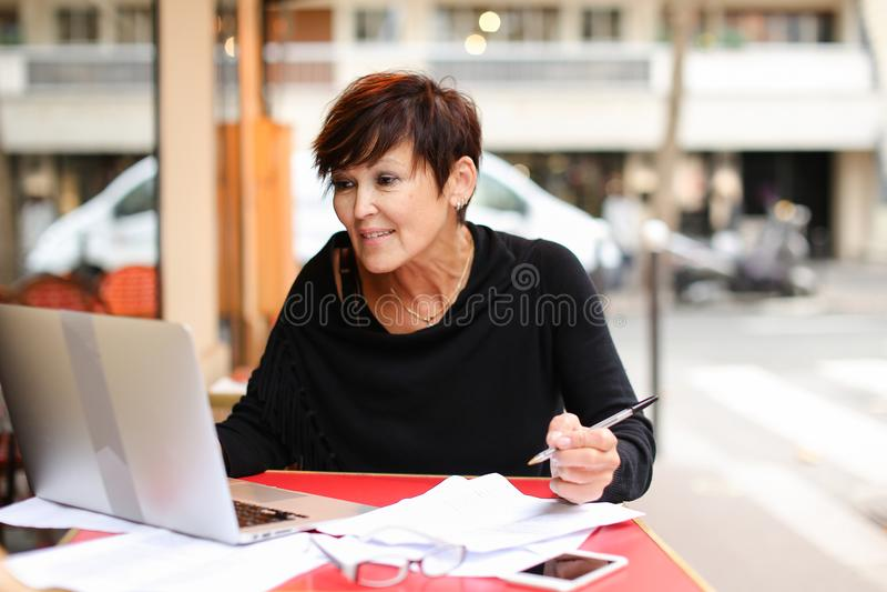 μέσος ηλικίας θηλυκός συμπληρωματικός σπουδαστής που χρησιμοποιεί το lap-top για στοκ φωτογραφίες με δικαίωμα ελεύθερης χρήσης