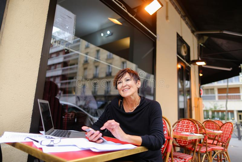 μέσος ηλικίας θηλυκός συμπληρωματικός σπουδαστής που χρησιμοποιεί το lap-top για στοκ εικόνες