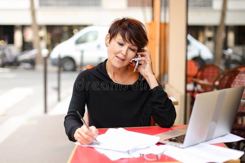 μέσος ηλικίας θηλυκός συμπληρωματικός σπουδαστής που χρησιμοποιεί το lap-top για στοκ εικόνα