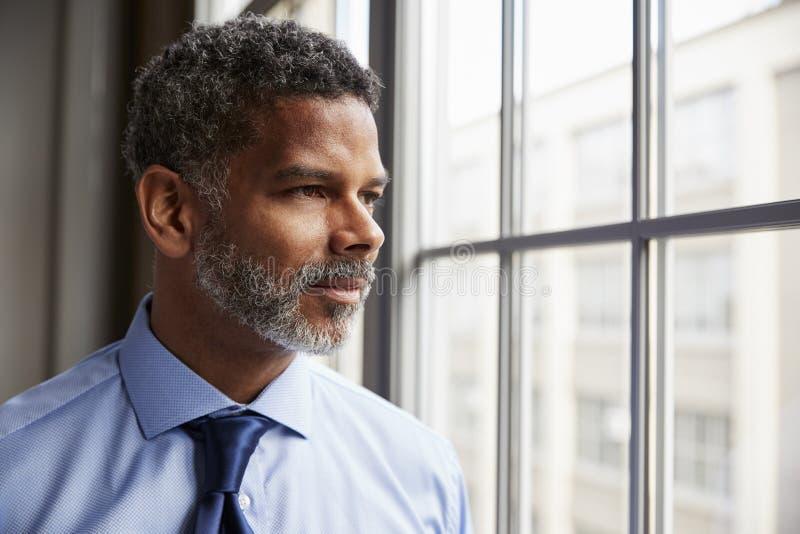 Μέσος ηλικίας μαύρος επιχειρηματίας που κοιτάζει από το παράθυρο στοκ εικόνες