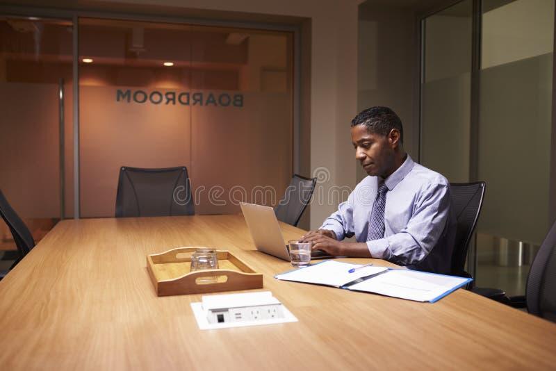 Μέσος ηλικίας μαύρος επιχειρηματίας που απασχολείται αργά μόνο σε στην αρχή στοκ φωτογραφίες