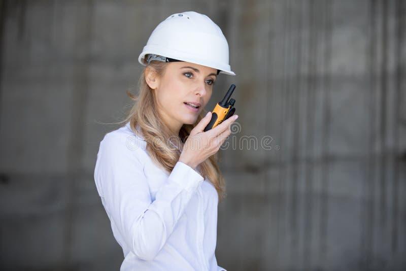 Μέσος ηλικίας μηχανικός στο σκληρό καπέλο που χρησιμοποιεί walkie-talkie εργαζόμενος στοκ εικόνες