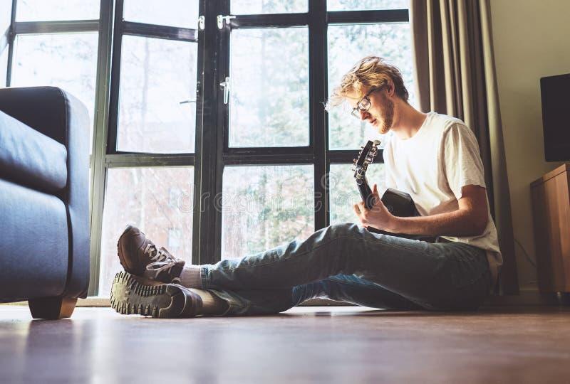 Μέσος πυροβολισμός των παιχνιδιών νεαρών άνδρων στη συνεδρίαση κιθάρων στο πάτωμα μέσα στοκ φωτογραφία