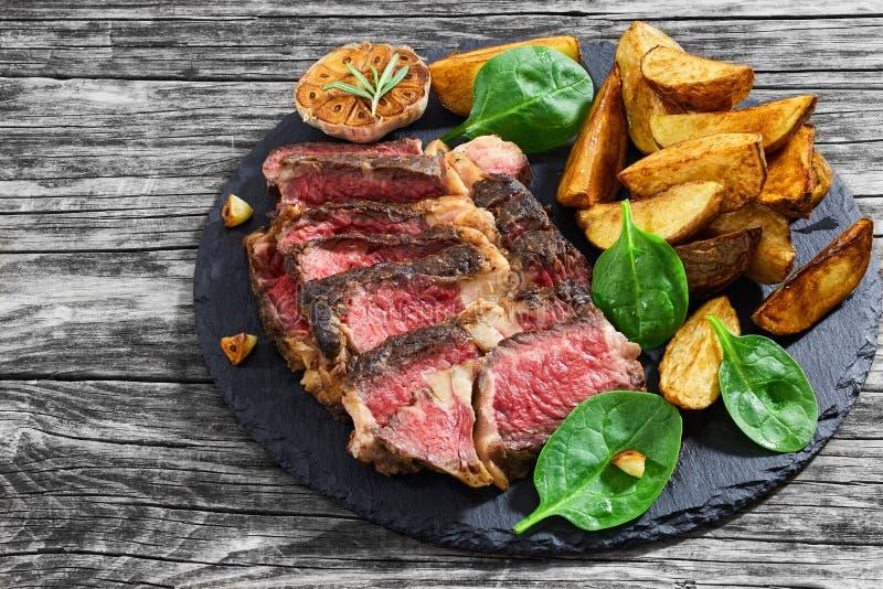 Μέσος σπάνιος μπριζόλας βόειου κρέατος με τα καρυκεύματα που κόβονται στις φέτες στοκ εικόνες