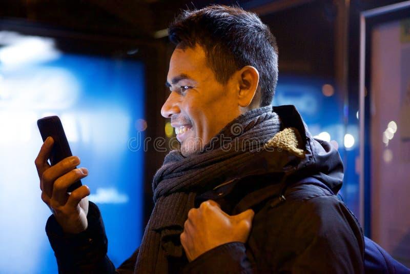 Μέσο ενήλικο ασιατικό άτομο που χρησιμοποιεί το τηλέφωνο κυττάρων στοκ φωτογραφία