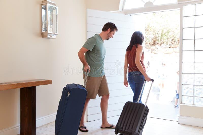 Μέσο ενήλικο λευκό ζεύγος στη μπροστινή πόρτα τους που αφήνει το σπίτι με τις αποσκευές για να πάει στις διακοπές, πλήρες μήκος στοκ εικόνες