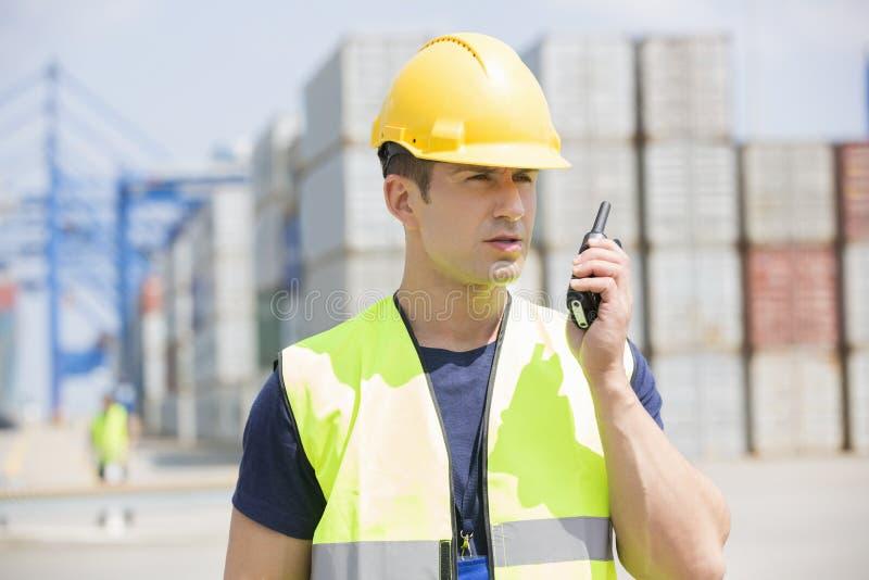Μέσο ενήλικο άτομο που χρησιμοποιεί walkie-talkie στη ναυτιλία του ναυπηγείου στοκ εικόνες με δικαίωμα ελεύθερης χρήσης