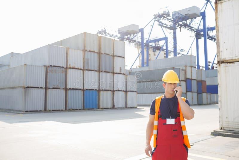 Μέσο ενήλικο άτομο που χρησιμοποιεί walkie-talkie στη ναυτιλία του ναυπηγείου στοκ φωτογραφίες με δικαίωμα ελεύθερης χρήσης