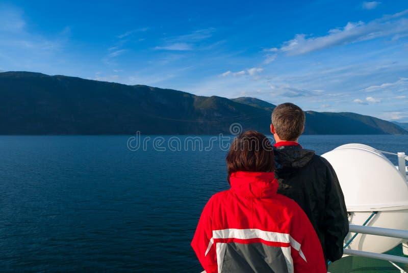 Μέσο ενήλικο ζεύγος που κοιτάζει επίμονα στο όμορφο Naeroyfjord στοκ φωτογραφία