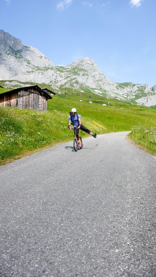Μέσο ηλικίας άτομο σε ένα κόκκινο scootor που συναγωνίζεται κάτω από έναν δρόμο βουνών στις Άλπεις κοντά σε Klosters μετά από τις στοκ εικόνες με δικαίωμα ελεύθερης χρήσης