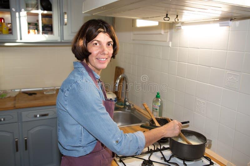 Μέσο ηλικίας μαγείρεμα γυναικών στην εγχώρια κουζίνα στοκ εικόνες