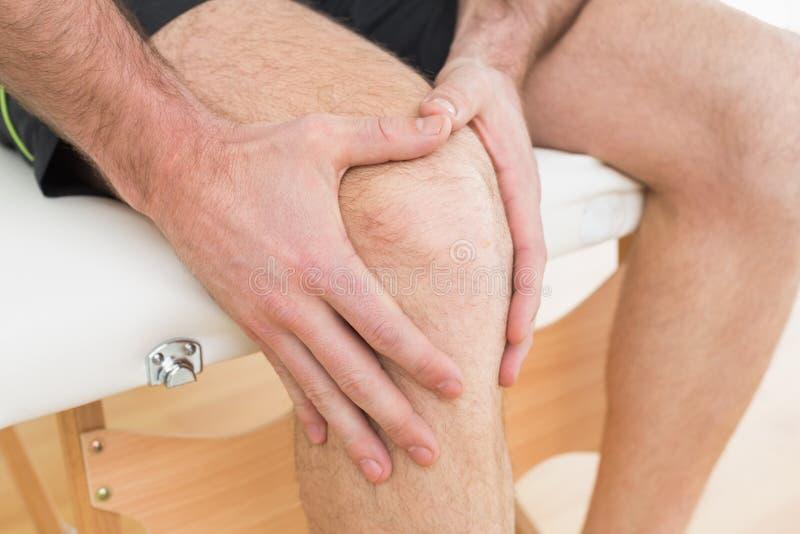 Μέσο τμήμα ενός ατόμου με τα χέρια του σε ένα επίπονο γόνατο στοκ εικόνα με δικαίωμα ελεύθερης χρήσης