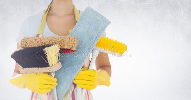 Μέσο τμήμα της γυναίκας που κρατά τους διάφορους καθαρίζοντας εξοπλισμούς στοκ φωτογραφία με δικαίωμα ελεύθερης χρήσης