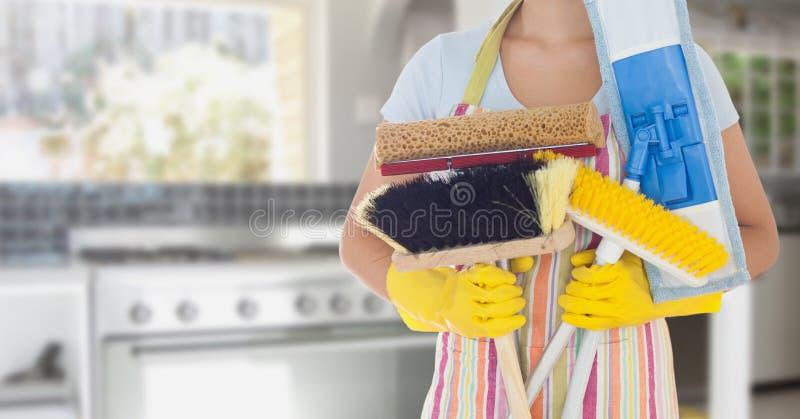 Μέσο τμήμα της γυναίκας που κρατά τους διάφορους καθαρίζοντας εξοπλισμούς στην κουζίνα στοκ εικόνες
