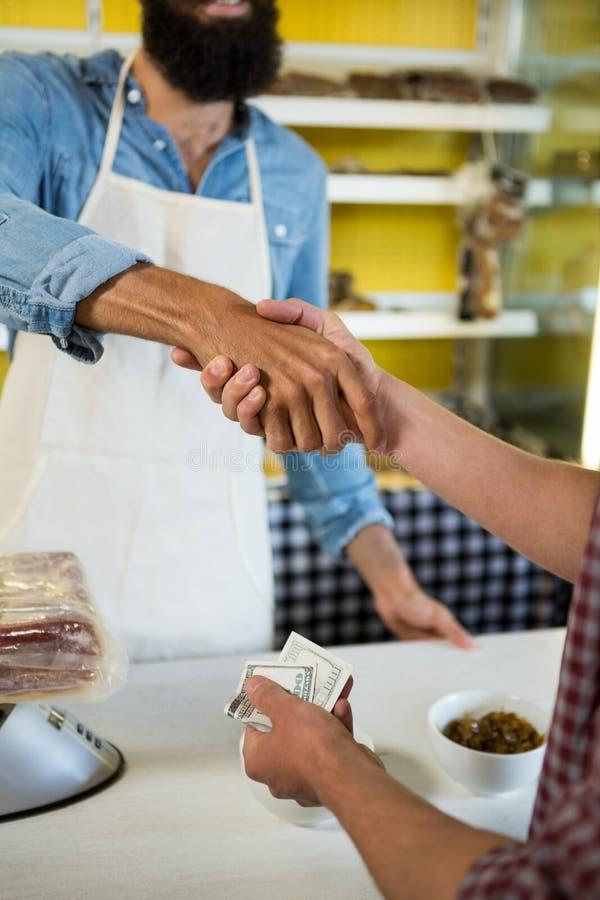 Μέσο τμήμα των χεριών τινάγματος προσωπικού και πελατών στο μετρητή κρέατος στοκ φωτογραφία με δικαίωμα ελεύθερης χρήσης