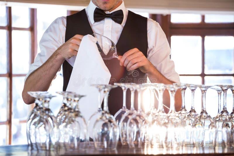 Μέσο τμήμα bartender καθαρίζοντας wineglass στοκ φωτογραφία με δικαίωμα ελεύθερης χρήσης