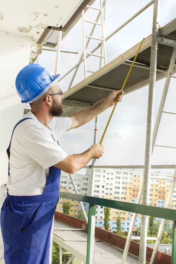 Μέτρηση απόστασης Εργασία για την περιοχή, εργαζόμενος στο μεγάλο υψόμετρο στα υλικά σκαλωσιάς στοκ εικόνες