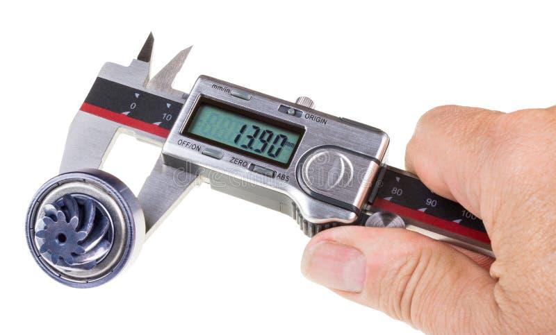 Μέτρηση της διαμέτρου gearwheel του άξονα από τους ψηφιακούς παχυμετρικούς διαβήτες στοκ εικόνα