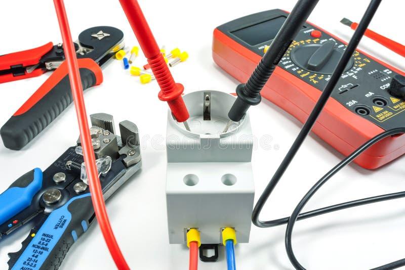 Μέτρηση της τάσης στην ηλεκτρική έξοδο με ένα πολύμετρο σε ένα άσπρο υπόβαθρο στοκ εικόνες