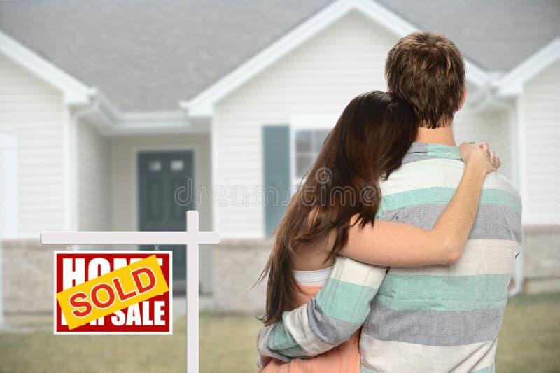 Μέτωπο ζεύγους INF του σπιτιού με το πωλημένο σημάδι στοκ φωτογραφία