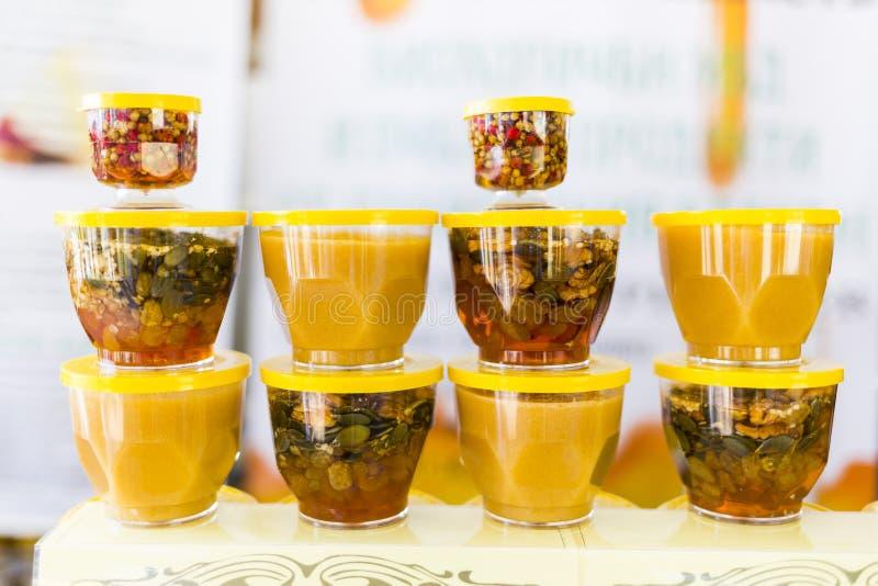 Μέλι με τους ξηρούς καρπούς και τα καρύδια στοκ εικόνες