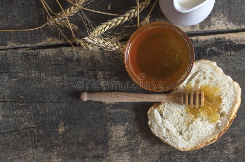 Μέλι σε ένα βάζο, ένα ψωμί, έναν σίτο και ένα γάλα στον ξύλινο πίνακα στοκ εικόνα
