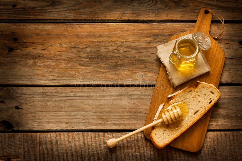 Μέλι σε ένα βάζο, τη φέτα του ψωμιού και dipper μελιού στο εκλεκτής ποιότητας ξύλο στοκ εικόνα