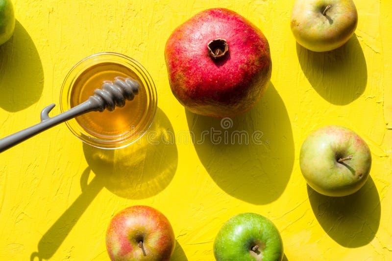 Μέλι σε ένα φλυτζάνι, ένα ρόδι και τα μήλα για το εβραϊκό νέο έτος στοκ εικόνα