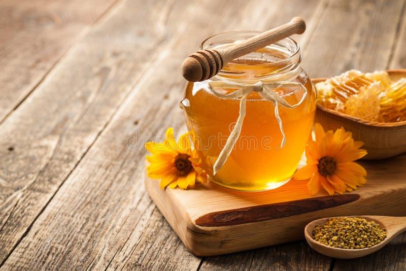Μέλι στο βάζο γυαλιού και κηρήθρα στον ξύλινο πίνακα στοκ εικόνα