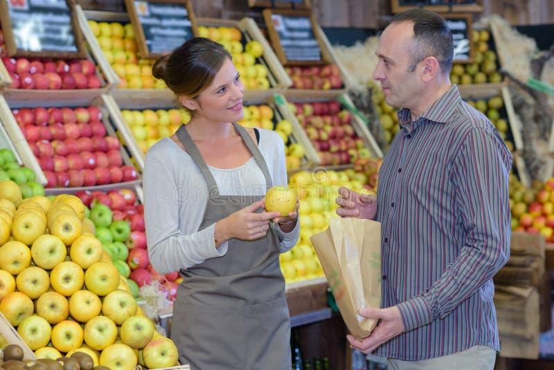 Μήλα αγοράς ατόμων greengrocers στοκ εικόνα