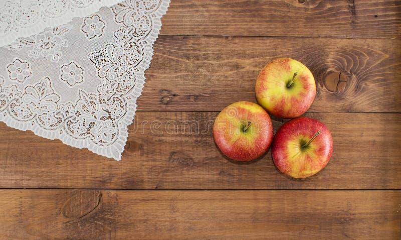 Μήλα σε μια ξύλινη πετσέτα υποβάθρου και δαντελλών Κατάλληλη διατροφή σιτηρέσιο υγιεινό χορτοφαγία Κατάλληλο πρόγευμα το σωστό πρ στοκ εικόνα με δικαίωμα ελεύθερης χρήσης