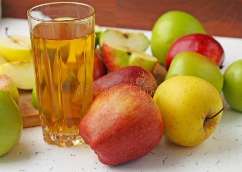 Μήλα στον πίνακα και ένα ποτήρι του χυμού μήλων στοκ εικόνα με δικαίωμα ελεύθερης χρήσης