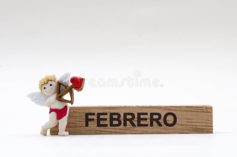Μήνας Φεβρουαρίου σε ένα ξύλινο ορθογώνιο και λίγο Cupid στοκ φωτογραφία με δικαίωμα ελεύθερης χρήσης