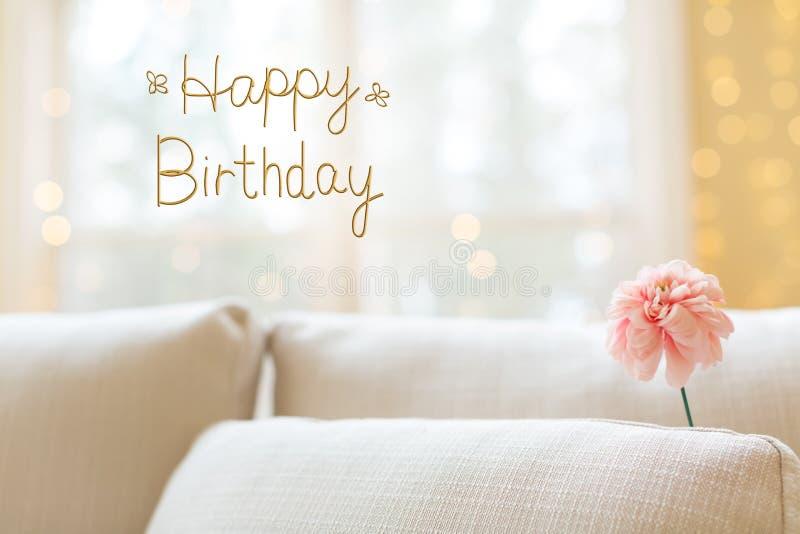 Μήνυμα γενεθλίων με το λουλούδι στον εσωτερικό καναπέ δωματίων στοκ φωτογραφίες