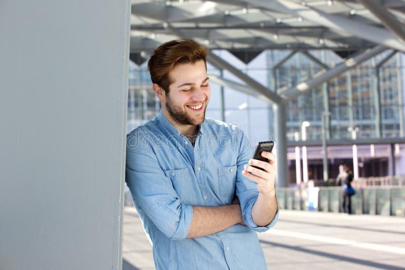 Μήνυμα κειμένου ανάγνωσης ατόμων χαμόγελου στο κινητό τηλέφωνο στοκ εικόνα με δικαίωμα ελεύθερης χρήσης