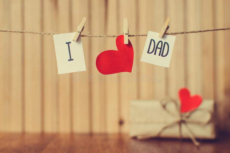Μήνυμα με την ένωση καρδιών εγγράφου με τα clothespins πέρα από τον ξύλινο πίνακα Χαιρετισμός ημέρας πατέρων E στοκ εικόνες