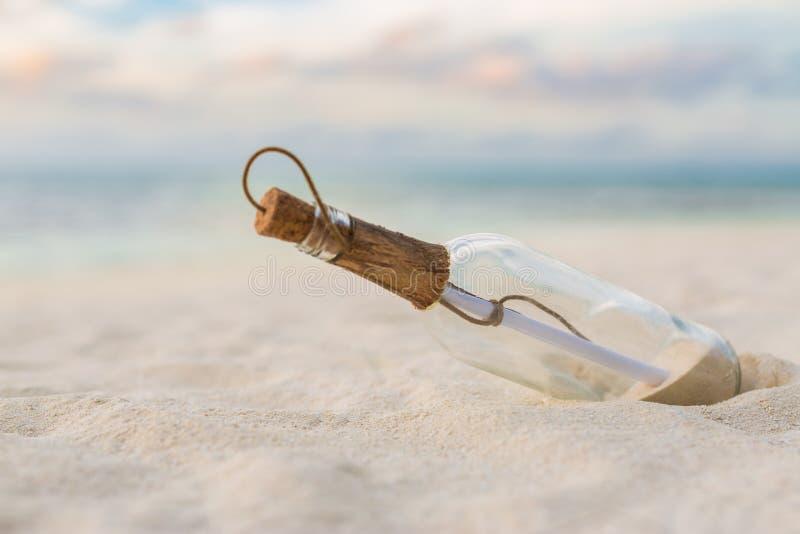 Μήνυμα σε ένα μπουκάλι σε μια τροπική παραλία και ένα θολωμένο υπόβαθρο Εμπνεύστε bckground το σχέδιο στοκ εικόνες