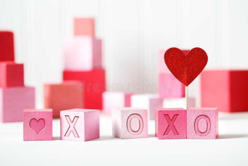 Μήνυμα XOXO με τους ρόδινους και κόκκινους φραγμούς στοκ φωτογραφία