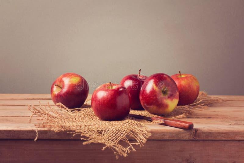 Μήλα στον ξύλινο πίνακα πέρα από το αναδρομικό υπόβαθρο στοκ φωτογραφία με δικαίωμα ελεύθερης χρήσης