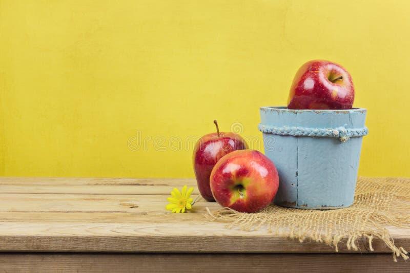 Μήλα στον ξύλινο πίνακα πέρα από το κίτρινο υπόβαθρο ταπετσαριών στοκ εικόνα