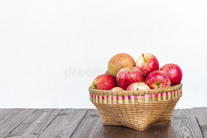 Μήλα στο ξύλινο καλάθι στο ξύλινο πάτωμα στοκ φωτογραφία με δικαίωμα ελεύθερης χρήσης