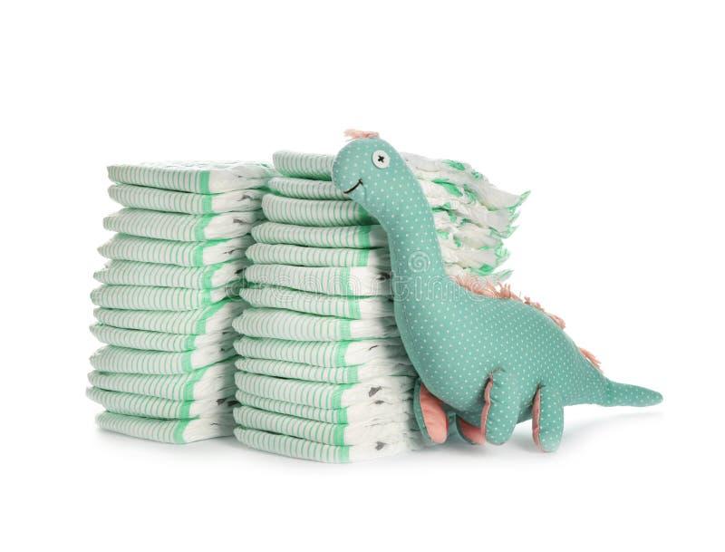 Μίας χρήσης πάνες και δεινόσαυρος παιχνιδιών στο λευκό Εξαρτήματα μωρών στοκ φωτογραφία με δικαίωμα ελεύθερης χρήσης